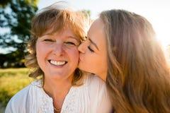 Felicidad - hija adolescente que besa a la madre Imágenes de archivo libres de regalías