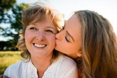 Felicidad - hija adolescente que besa a la madre Imagen de archivo libre de regalías