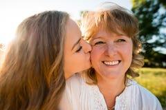Felicidad - hija adolescente que besa a la madre Imagenes de archivo