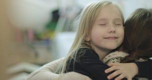 Felicidad y amor La pequeña hija acomete en los brazos del ` s de la madre en casa y le da un abrazo grande metrajes
