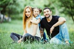 Felicidade e harmonia na vida familiar Conceito de família feliz Mãe e pai novos com sua filha no parque Família feliz Fotografia de Stock