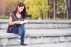 Felicidade e sorriso adolescentes asiáticos do livro de leitura das mulheres Foto de Stock Royalty Free