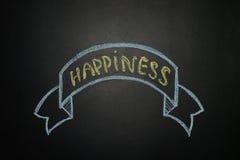 Felicità con l'insegna del nastro, scritta con gesso su una lavagna Immagine Stock