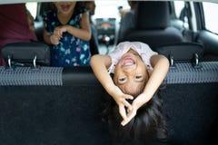 Felicità della figlia sullo sguardo della parte posteriore di sedile di nuovo al bagaglio con la posizione di salto mortale fotografia stock