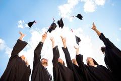 Felicitações aos graduados! Baixo ângulo disparado do grupo alegre o fotografia de stock