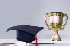 Felicite al graduado Trofeo y sombrero negro en fondo imagen de archivo