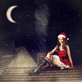 Felik kvinna för jul i röd klänning och den santa hatten Fotografering för Bildbyråer