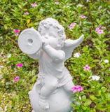 Felik staty i trädgården med blomman Fotografering för Bildbyråer