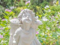 Felik staty i trädgården med blomman Arkivfoto