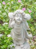 Felik staty i trädgården med blomman Arkivbilder