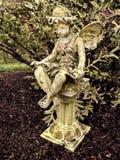 Felik staty på pelare i trädgård fotografering för bildbyråer