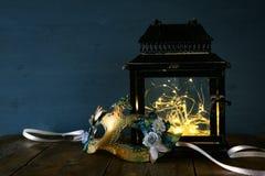 felika ljus inom den gamla lyktan och den venetian maskeringen Arkivfoto