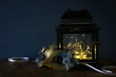 felika ljus inom gammal lykta- och maskeradmaskering Royaltyfria Bilder