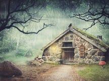 Felikt gammalt stenhus i fantasiskog med dimma royaltyfri bild