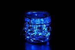 Felikt ljus i en exponeringsglaskrus med locket som isoleras p? svart bakgrund arkivbilder