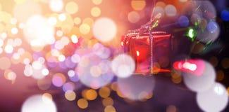 Felikt ljus och liten gåvaask som hänger på julträd Arkivfoto