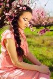 Felikt sammanträde för ung kvinna i blossomy trädgård Arkivbild