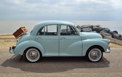 Classic Light Blue Morris Minor with picnic basket parked on seafront promenade. Royalty Free Stock Photography