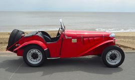 Classic Red Delon Sports - Trials Motor Car Parked on Seafront Promenade. Stock Photography