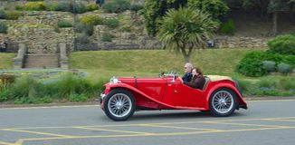 Classic Red  MG Sports car  being driven along road. Stock Images