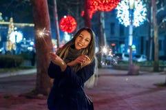 Feliz Año Nuevo Ciérrese para arriba de la mujer que sostiene la bengala en la calle Foto de archivo libre de regalías