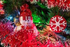 Feliz Año Nuevo con el árbol imperecedero, juguetes del muñeco de nieve y del copo de nieve e iluminación colorida en paleta roja Fotografía de archivo libre de regalías