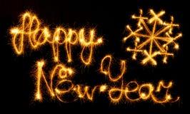 Feliz Año Nuevo con el copo de nieve hecho con las chispas en negro Fotografía de archivo