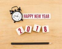 Feliz Año Nuevo 2018 con el cubo del despertador y de madera en etiqueta de la oficina Fotos de archivo libres de regalías