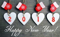 Feliz Año Nuevo 2018 Corazones de madera blancos decorativos de la Navidad y manoplas rojas en viejo fondo de madera Imagen de archivo