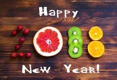 Feliz Año Nuevo 2018 de la fruta y de las bayas en fondo de madera Foto de archivo
