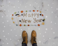 Feliz Año Nuevo de la inscripción del inconformista escrita en la nieve y las botas amarillas Fotos de archivo libres de regalías