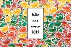 Feliz Año Nuevo de la tarjeta del nuevo 2019 del año de Feliz en español con las hojas coloreadas del acebo como fondo stock de ilustración