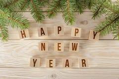 Feliz Año Nuevo de los saludos del Año Nuevo, creativa la inscripción en los cubos Fondo de madera con las ramas de la picea azul Imágenes de archivo libres de regalías