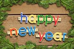 Feliz Año Nuevo del texto del saludo con un marco hecho de picea Foto de archivo
