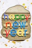 Feliz Año Nuevo del texto del saludo en el bosque en un marco nevoso Imagen de archivo
