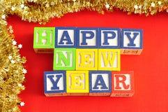 Feliz Año Nuevo deletreada con los bloques del alfabeto y la malla de oro Imagen de archivo libre de regalías