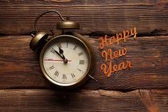 Feliz Año Nuevo - despertador en fondo de madera Imagenes de archivo