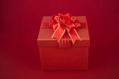 Feliz Año Nuevo en la caja y la tarjeta rojas de regalo en fondo rojo Imagenes de archivo