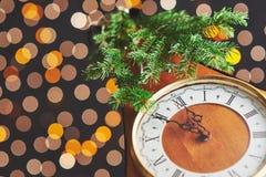 Feliz Año Nuevo en la medianoche 2018, el reloj de madera viejo con las luces del día de fiesta y el abeto ramifica Imágenes de archivo libres de regalías