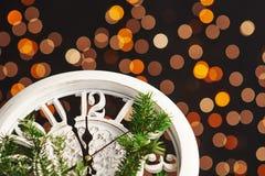 Feliz Año Nuevo en la medianoche 2018, el reloj de madera viejo con las luces del día de fiesta y el abeto ramifica Fotos de archivo libres de regalías