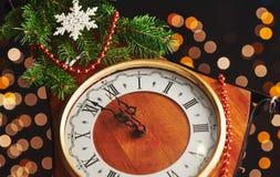 Feliz Año Nuevo en la medianoche 2018, el reloj de madera viejo con las luces del día de fiesta y el abeto ramifica Imagen de archivo libre de regalías