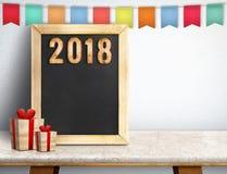 Feliz Año Nuevo 2018 en la pizarra con el regalo y vagos coloridos de la bandera Imágenes de archivo libres de regalías
