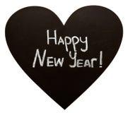 Feliz Año Nuevo en la pizarra de la forma del corazón imagenes de archivo