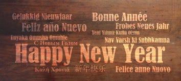 Feliz Año Nuevo en muchas idiomas en fondo de madera Imagenes de archivo