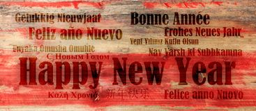 Feliz Año Nuevo en muchas idiomas en fondo de madera rojo Imágenes de archivo libres de regalías