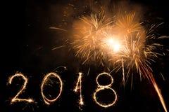 Feliz Año Nuevo 2018 escrita con el fuego artificial de la chispa y los fuegos artificiales coloridos como fondo Imágenes de archivo libres de regalías