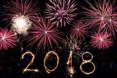 Feliz Año Nuevo 2018 escrita con el fuego artificial de la chispa y los fuegos artificiales coloridos como fondo Imagen de archivo libre de regalías