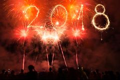 Feliz Año Nuevo 2018 escrita con las bengalas y los fuegos artificiales coloridos como fondo Celebración de gente del partido Fotografía de archivo libre de regalías