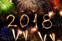 Feliz Año Nuevo 2018 escrita con las chispas y los fuegos artificiales coloridos como fondo Fotos de archivo libres de regalías