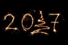 FELIZ AÑO NUEVO 2017 escrita con los fuegos artificiales como fondo Imagen de archivo libre de regalías